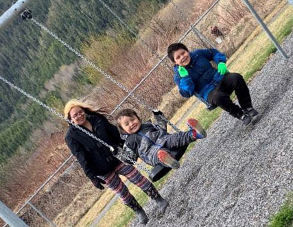 FNHA-Laxgaltsap-kids-on-swings-with-parent.JPG